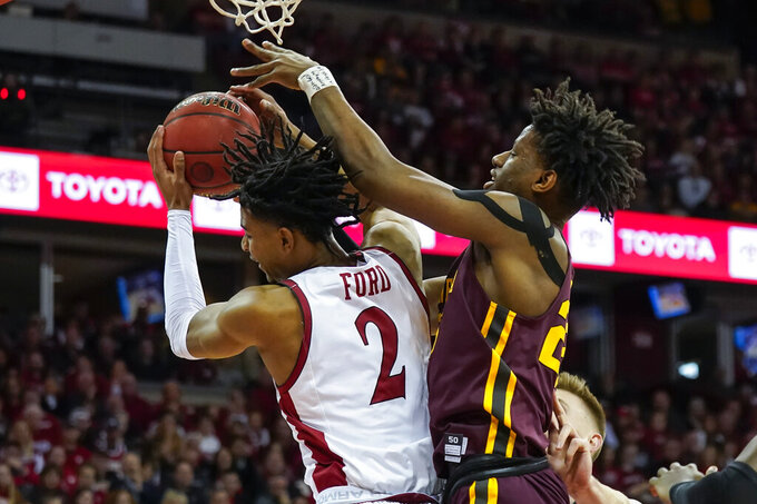 Wisconsin's Aleem Ford (2) grabs a defensive rebound against Minnesota's Daniel Oturu (25) during the first half of an NCAA college basketball game Sunday, March 1, 2020, in Madison, Wis. (AP Photo/Andy Manis)