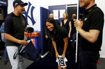 Britain's Prince Harry and Meghan, Duchess of Sussex receive a present for baby Archie as they meet players of the New York Yankees before a match against the Boston Red Sox in London, Saturday June 29, 2019. (Peter Nicholls/Pool via AP)