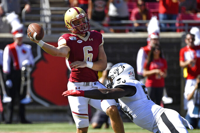Boston College quarterback Dennis Grosel (6) attempts to get rid of the ball before being brought down by Louisville defensive lineman Amonte Caban (53) during the first half of an NCAA college football game in Louisville, Ky., Saturday, Oct. 5, 2019. (AP Photo/Timothy D. Easley)