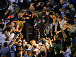 People surround fallen riot police officers during a charge to clear the square during protests outside the government headquarters, in Bucharest, Romania, Friday, Aug. 10, 2018. Romanians who live abroad are staging an anti-government protest calling on the left-wing government to resign and an early election. (AP Photo/Vadim Ghirda)