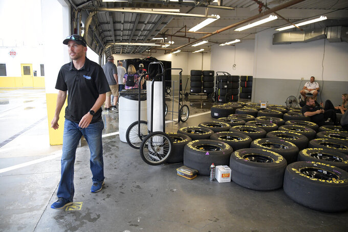 Driver Ross Chastain, left, walks through the garage area during a rain delay before a NASCAR Cup Series auto race at Daytona International Speedway, Saturday, July 6, 2019, in Daytona Beach, Fla. (AP Photo/Phelan M. Ebenhack)