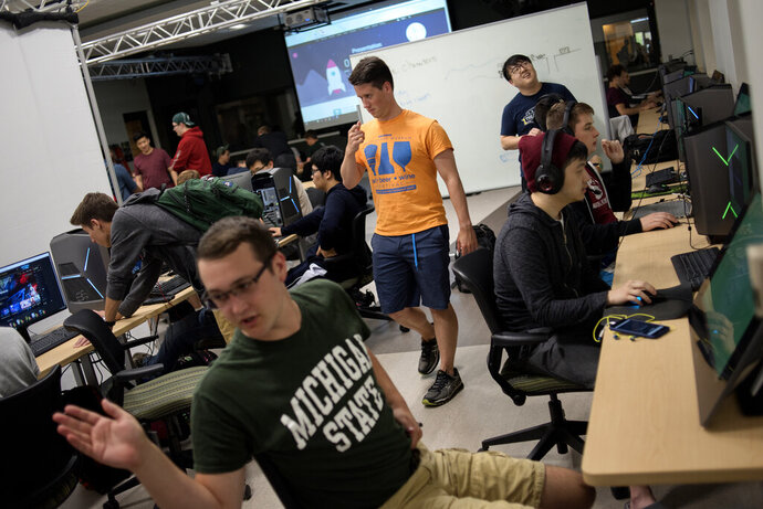 "FILE - In this Sept. 13, 2017, file photo, Kyle Kilponen, center, at the time a senior and coach for the competitive League of Legends team, prepares for team tryouts during a gathering of gamers in the Communication Arts and Sciences building on the Michigan State Campus in East Lansing. A month after the NCAA voted to table a discussion regarding esports, ""League of Legends"" publisher Riot Games has launched a governing body for its college and high school competitive video game activities. The Riot Scholastic Association of America will feature a six-member advisory board that oversees all ""League of Legends"" college competition, the company announced Wednesday. May 22, 2019. (Nick King/Lansing State Journal via AP, File)"