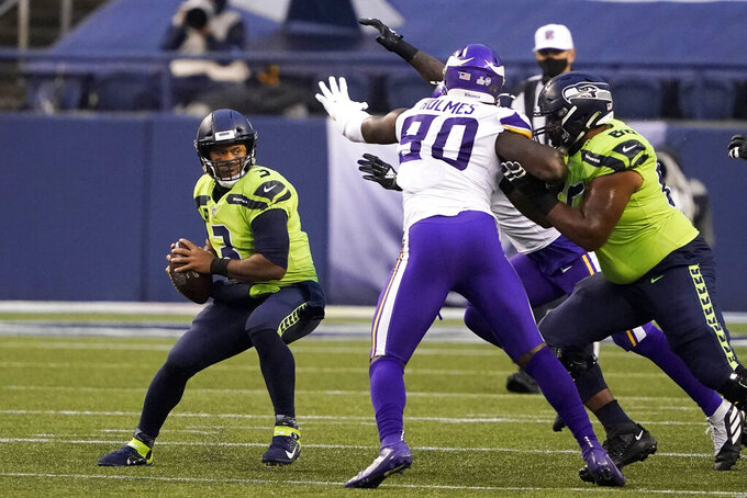 Seattle Seahawks quarterback Russell Wilson, left, looks for room to pass against pressure from the Minnesota Vikings during the first half of an NFL football game, Sunday, Oct. 11, 2020, in Seattle. (AP Photo/Ted S. Warren)