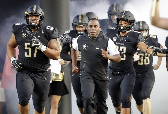 FILE - In this Sept. 1, 2018, file photo, Vanderbilt coach Derek Mason, center, runs onto the field with his team before its opening game of the NCAA college football season, against Middle Tennessee, in Nashville, Tenn. New Vanderbilt athletic director Malcolm Turner has extended the contract for coach Derek Mason after the Commodores reached a second bowl game in three seasons. Turner also announced Friday, Feb. 22, 2019, extensions for men's golf coach Scott Limbaugh and bowling coach John Williamson.(AP Photo/Mark Humphrey, File)