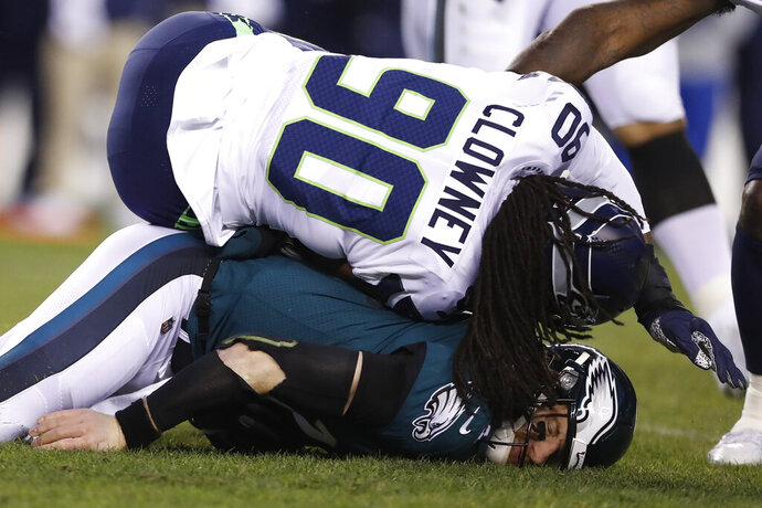 FILE - In this Jan. 5, 2020, file photo, Philadelphia Eagles' Carson Wentz is hit by Seattle Seahawks' Jadeveon Clowney (90) during the first half of an NFL wild-card playoff football game in Philadelphia. The Browns remain interested in Clowney, the talented defensive end _ and former No. 1 overall draft pick _ who remains unsigned and the top target on the free agent market. During a Zoom meeting with reporters on Thursday, May 28, 2020, Browns new defensive coordinator Joe Wood praised Clowney but deferrred any questions about the Browns' pursuit of the speedy edge rusher to general manager Andrew Berry.(AP Photo/Julio Cortez, File)