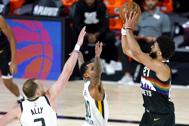 Denver Nuggets' Jamal Murray, right, shoots against Utah Jazz's Joe Ingles, left, and Jordan Clarkson during overtime in an NBA basketball first round playoff game, Monday, Aug. 17, 2020, in Lake Buena Vista, Fla. The Nuggets won 135-125 in overtime. (AP Photo/Ashley Landis, Pool)