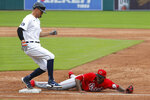Cincinnati Reds relief pitcher Raisel Iglesias, right, stretches to cover first base for an out on a Detroit Tigers' JaCoby Jones ground ball in the seventh inning of the first baseball game of a doubleheader in Detroit, Sunday, Aug. 2, 2020. (AP Photo/Paul Sancya)