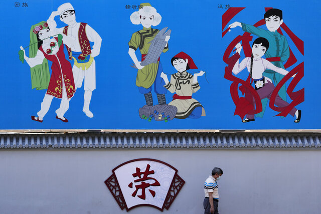 A man wearing a face mask to protect against the new coronavirus walks by a mural depicting various cultural dance on display on a street in Beijing, Tuesday, Aug. 4, 2020. Both mainland China and Hong Kong reported fewer new cases of COVID-19 on Tuesday as strict measures to contain new infections appear to be taking effect. (AP Photo/Andy Wong)