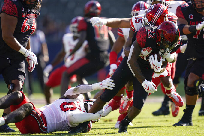 San Diego State running back Greg Bell (22) is tackled by Utah linebacker Devin Lloyd (0) and cornerback Malone Mataele (15) during the first half of an NCAA college football game Saturday, Sept. 18, 2021, in Carson, Calif. (AP Photo/Ashley Landis)
