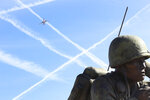 """In this Friday, Feb. 9, 2018 photo, a low-flying jetliner that just took off from Phoenix Sky Harbor International Airport banks over the Navajo Code Talkers memorial at the Arizona Capitol. Last year's court victory by Phoenix and neighborhood groups over the Federal Aviation Administration has prompted the agency to be more responsive to residents as it continues to beat back noise complaints around the United States over the air traffic modernization plan known as """"NextGen."""" (AP Photo/Bob Christie)"""