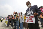 South Korean protesters take a moment of silence during a protest over the death of George Floyd, a black man who died after being restrained by Minneapolis police officers on May 25, near the U.S. embassy in Seoul, South Korea, Friday, June 5, 2020. The signs read