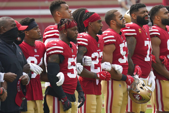 San Francisco 49ers players and coaches lock arms while standing during a presentation on social justice before an NFL football game against the Arizona Cardinals in Santa Clara, Calif., Sunday, Sept. 13, 2020. (AP Photo/Tony Avelar)