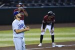 Los Angeles Dodgers starting pitcher Clayton Kershaw rubs up a new baseball after giving up an RBI triple to Arizona Diamondbacks' Tim Locastro, who stands next to Diamondbacks third base coach Tony Perezchica during the second inning of a baseball game Wednesday, Sept. 9, 2020, in Phoenix. (AP Photo/Ross D. Franklin)