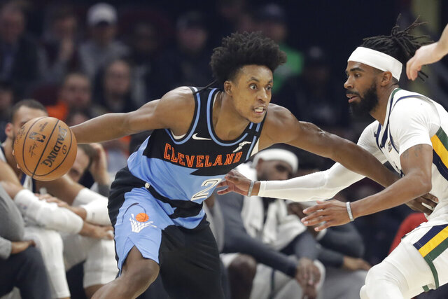 "FILE - In this March 2, 2020, file photo, Cleveland Cavaliers' Collin Sexton, left, drives past Utah Jazz's Mike Conley in the first half of an NBA basketball game in Cleveland. When Sexton learned that the NBA _ and not a virus _ had ended his second season, the Cavaliers guard had a guttural reaction. ""I was sick,"" he said. The league's decision to only invite 22 teams to resume play at Disney World in Florida next month was a body blow for players on the omitted squads _ aka the Delete 8. And although they've had time to process the exclusion, Sexton, Cavs star forward Kevin Love and their teammates, are still struggling with the reality that their season is over. (AP Photo/Tony Dejak, File)"