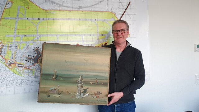 In this photo released by the police department in Duesseldorf on Thursday Dec. 10, 2020, showing Chief Detective Michael Dietz holding a painting from French artist Yves Tanguy.  A businessman, whose identity was not given, boarded a flight from Duesseldorf to Tel Aviv on Nov. 27, but forgot the painting by French surrealist Yves Tanguy, which was wrapped in cardboard, on the check-in counter. By the time he landed in Israel and contacted Duesseldorf police, the 280,000 Euro, (dollar 340,000), oeuvre had disappeared but was later found at a nearby paper dumpster, Duesseldorf police said. (Polizei Duesseldorf via AP)
