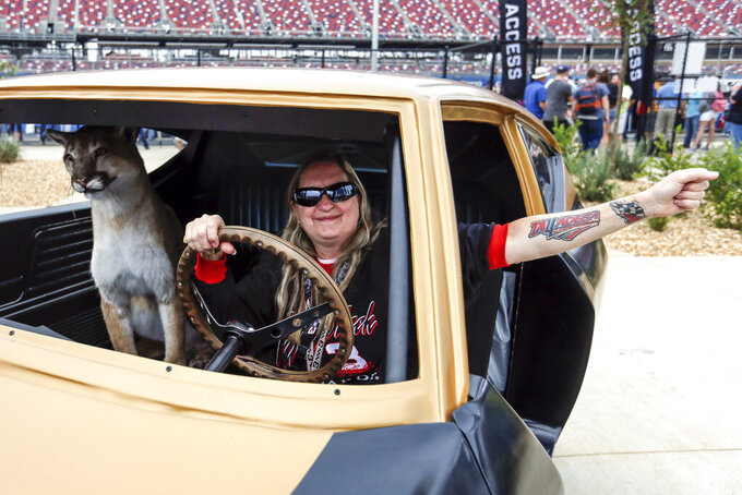 "Holli Ballien, of Mobile, poses with a ""Karen the cougar"" taxidermy as fans enjoy the new facilities and garages at Talladega Superspeedway, Saturday, Oct. 12, 2019, in Talladega, Ala. (AP Photo/Butch Dill)"