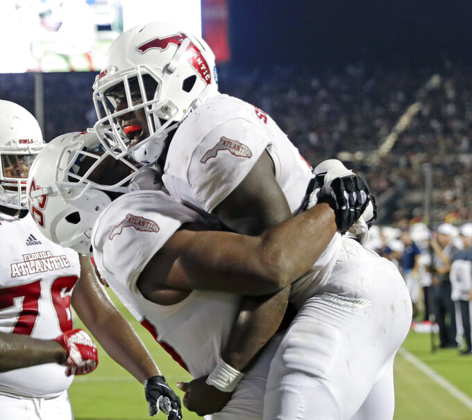 Florida Atlantic running back Devin Singletary, right, gets a hug from offensive lineman Antonio Riles after he ran a 9-yard touchdown against Central Florida during the first half of an NCAA college football game, Friday, Sept. 21, 2018, in Orlando, Fla. (AP Photo/John Raoux)