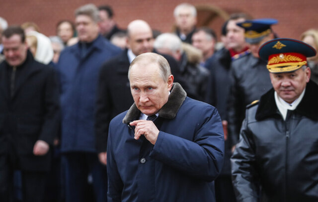 Russian President Vladimir Putin, centre, attends a wreath-laying ceremony at the Tomb of the Unknown Soldier, near the Kremlin during the national celebrations of the 'Defender of the Fatherland Day' in Moscow, Russia, Sunday, Feb. 23, 2020. The Defenders of the Fatherland Day, celebrated in Russia on Feb. 23, honors the nation's military and is a nationwide holiday. (Yuri Kochetkov/Pool Photo via AP)
