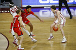 CORRECTS SPELLING TO REAVES, INSTEAD OF REEVES - Oklahoma's Austin Reaves (12) watches as Kur Kuath (52) moves between Texas Tech's Mac McClung (0) and Terrence Shannon Jr. (1) during the first half of an NCAA college basketball game in Norman, Okla., Tuesday, Dec. 22, 2020. (AP Photo/Garett Fisbeck)