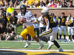 West Virginia quarterback Austin Kendall, left, looks for an open receiver as he runs from Missouri's Khalil Oliver, right, during the first half of an NCAA college football game Saturday, Sept. 7, 2019, in Columbia, Mo. (AP Photo/L.G. Patterson)