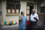 In this July 18, 2019, photo, retired Indian civil servant R. Devarajan, right, talks with his wife Padmini, in the alley of their locality in Chennai, India. For Devarajan and Padmini, Chennai's acute water shortage has reinforced the wisdom of their decision years ago to install a rainwater harvesting system in their three-story home. (AP Photo/Manish Swarup)