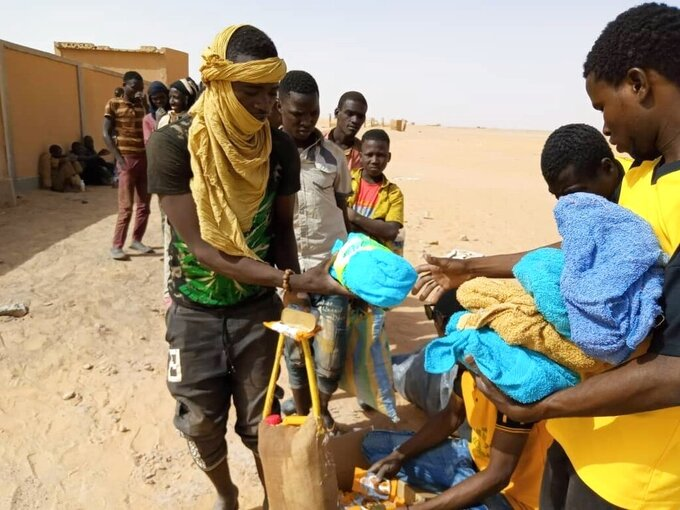 In this April 25, 2020 photo provided by IOM Niger, some of nearly 100 Nigeriens arrive in Assamaka, Niger, on foot from Algeria and now must be quarantined for two weeks at the remote Sahara border settlement, where water is scarce and midday temperatures reach over 110 degrees (45 degrees Celsius). Globally, coronavirus has marooned thousands of migrants in some of the world's harshest conditions on land and at sea. (IOM Niger via AP)