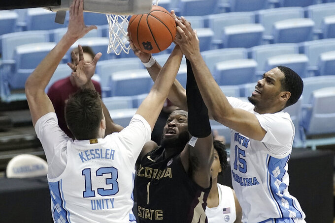 North Carolina forwards Walker Kessler (13) and Garrison Brooks (15) block Florida State forward RaiQuan Gray (1) during the second half of an NCAA college basketball game in Chapel Hill, N.C., Saturday, Feb. 27, 2021. (AP Photo/Gerry Broome)