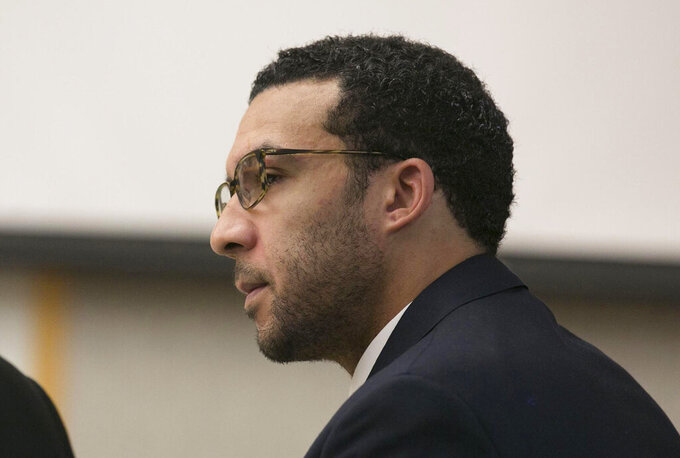 FILE - In this May 20, 2019 file photo Former NFL football player Kellen Winslow Jr. looks at attorney Marc Carlos during his rape trial in Vista, Calif.  Prosecutors are expected to announce, Friday, June 14,  whether they will retry Winslow Jr. on eight criminal charges left undecided by the jury that convicted the former NFL player of rape. Winslow was convicted Monday of raping a 58-year-old homeless woman and two counts of lewd conduct involving two other women. The jury deadlocked on remaining charges, including two counts of rape involving a hitchhiker and an unconscious teenage girl.  (John Gibbins/The San Diego Union-Tribune via AP, Pool,File)