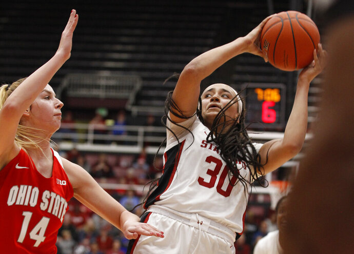 Stanford's Haley Jones (30) looks to pass next to Ohio State's Dorka Juhasz during the first half of an NCAA college basketball game Sunday, Dec. 15, 2019, in Stanford, Calif. (AP Photo/George Nikitin)