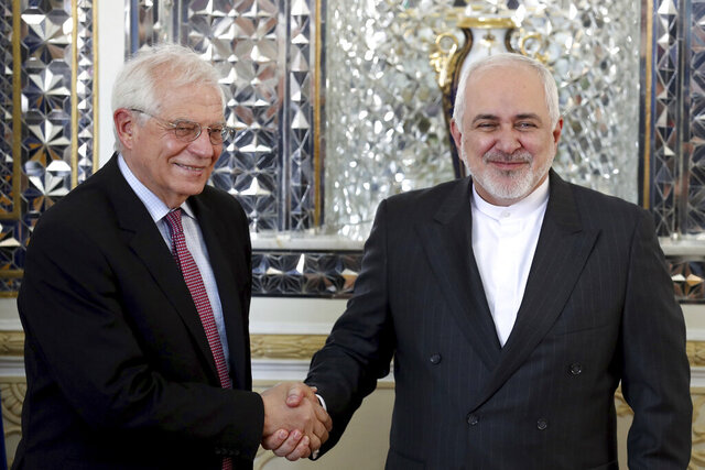 FILE - In this Monday, Feb 3, 2020, file photo, Iranian Foreign Minister Mohammad Javad Zarif, right, and European Union foreign policy chief Josep Borrell, shake hands for journalists prior to their meeting, in Tehran, Iran. Now that Britain has left the bloc, the EU hopes to find more time concentrate on its foreign policy. (AP Photo/Ebrahim Noroozi, File)