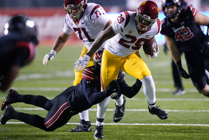Southern California running back Vavae Malepeai (29) drags a Utah player along on a carry during the first half during an NCAA college football game Saturday, Nov. 21, 2020, in Salt Lake City. (AP Photo/Rick Bowmer)