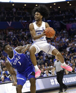 North Carolina's Coby White (2) drives to the basket against Duke's Zion Williamson (1) during the second half of an NCAA college basketball game in the Atlantic Coast Conference tournament in Charlotte, N.C., Friday, March 15, 2019. (AP Photo/Chuck Burton)