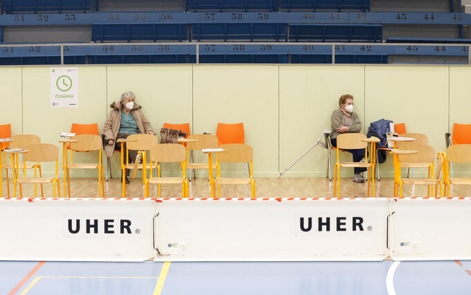 Elderly residents sit and wait after receiving Moderna COVID-19 vaccine at a sports hall in Ricany, Czech Republic, Friday, Feb. 26, 2021. With new infections soaring due to a highly contagious coronavirus variant and hospitals filling up, one of the hardest-hit countries in the European Union is facing inevitable: a tighter lockdown. (AP Photo/Petr David Josek)