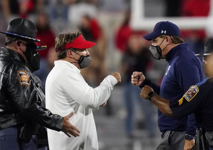 Georgia coach Kirby Smart, left, and Auburn coach Gus Malzahn, right, meet after an NCAA college football game Saturday, Oct. 3, 2020, in Athens, Ga. (AP Photo/Brynn Anderson)