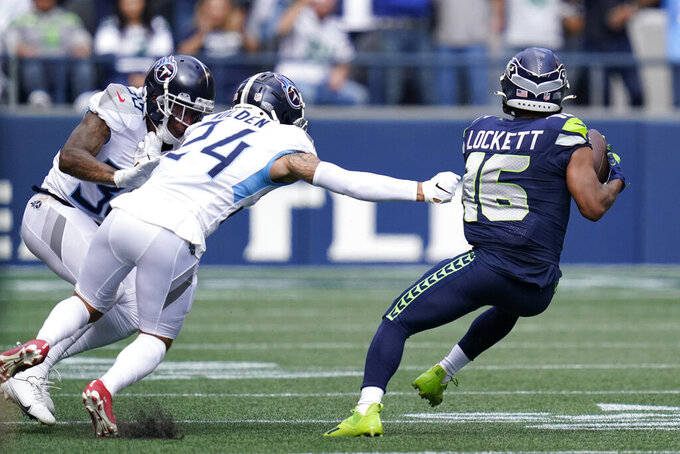 Seattle Seahawks wide receiver Tyler Lockett (16) breaks from the grasp of Tennessee Titans cornerback Elijah Molden (24) as he runs for a touchdown after a reception during the first half of an NFL football game, Sunday, Sept. 19, 2021, in Seattle. (AP Photo/Elaine Thompson)