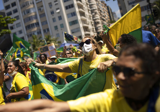 A woman wears a surgical mask during a rally supporting Brazil's President Jair Bolsonaro on Copacabana beach, Rio de Janeiro, Brazil, Sunday, March 15, 2020. Thousands took to the streets on Sunday to demonstrate in favor of Bolsonaro, challenging in some states the ban on agglomerations due to coronavirus and ignoring his suggestion to postpone the acts. (AP Photo/Silvia Izquierdo)