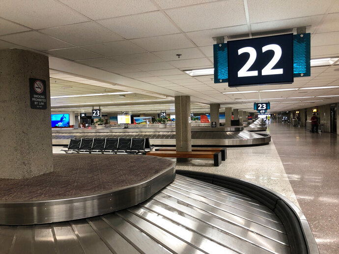This photo shows a deserted baggage claim lobby at Honolulu's Daniel K. Inouye International Airport on Thursday, March 26, 2020 as the state of Hawaii imposed a 14-day traveler quarantine to slow the coronavirus. Travelers landed in Hawaii to a new requirement that they hole up in hotel rooms or their homes for 14 days to fight the spread of the virus. (AP Photo/Audrey McAvoy)