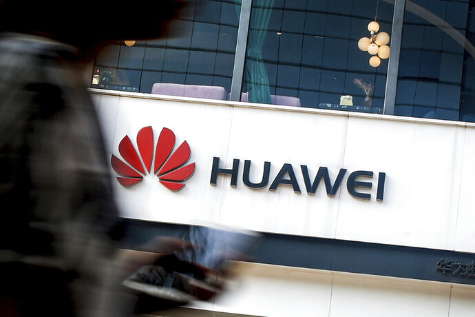FILE - In this July 30, 2019, file photo a woman walks by a Huawei retail store in Beijing. U.S. regulators are proposing to cut off funding for Chinese equipment in U.S. networks, citing security threats. The proposal would mean that telecom companies receiving government subsidies can't use those to pay for networking equipment from Huawei and ZTE. (AP Photo/Andy Wong, File)