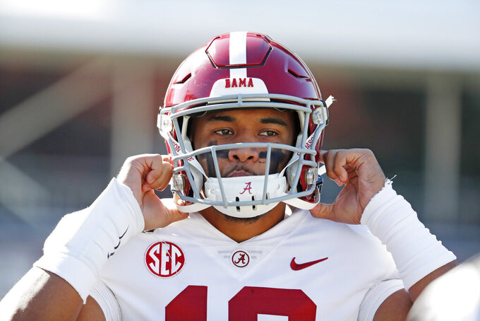 FILE - In this Nov. 16, 2019, file photo, Alabama quarterback Tua Tagovailoa (13) adjusts his helmet before an NCAA college football game against Mississippi State in Starkville, Miss. Miami Dolphins newcomer Tua Tagovailoa is starting to connect with his receivers. And for now, veteran receiver Albert Wilson said Wednesday, May 13, 2020 long-distance hookups with the rookie quarterback will have to do. (AP Photo/Rogelio V. Solis, Fle)