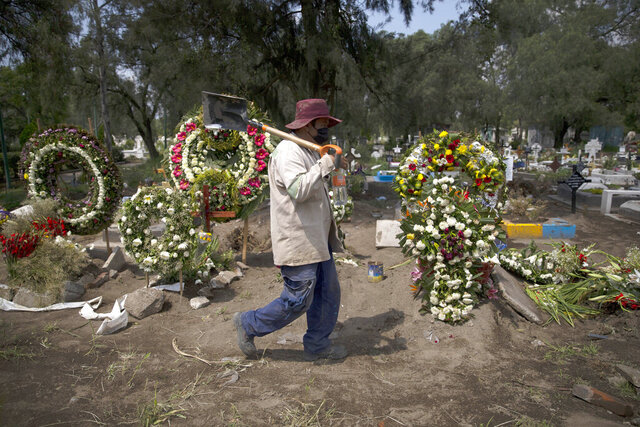 A grave digger walks in the COVID-19 section of the cemetery of San Lorenzo Tezonco Iztapalapa on the outskirts of Mexico City, Tuesday, Sept. 1, 2020. (AP Photo/Marco Ugarte)