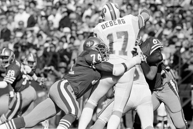FILE - In this Nov. 18, 1984, file photo, San Francisco 49ers defensive end Fred Dean (74) brings down Tampa Bay Buccaneers quarterback Steve DeBerg (17) for a loss during the first half of their NFL game at Candlestick Park, in San Francisco. Dean, the fearsome pass rusher who was a key part of the launch of the San Francisco 49ers' dynasty, has died. He was 68. His death on Wednesday night, Oct. 14, 2020, was confirmed Thursday by the Pro Football Hall of Fame in Canton, Ohio. (AP Photo/Eric Risberg, File)