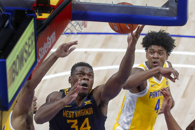 West Virginia's Oscar Tshiebwe (34) scores past Pittsburgh's Gerald Drumgoole Jr. (4) during the second half of an NCAA college basketball game, Friday, Nov. 15, 2019, in Pittsburgh. (AP Photo/Keith Srakocic)