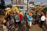 Rescuers gather at the site of a collapsed building in Preah Sihanouk province, Cambodia, Sunday, June 23, 2019. Rescue workers were using saws to cut steel beams and excavators to move piles of rubble of the collapsed seven-story building. (AP Photo/Heng Sinith)