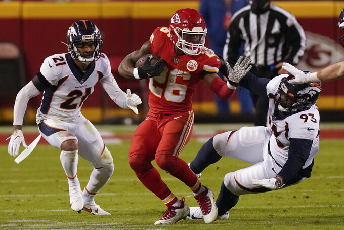 Kansas City Chiefs running back Le'Veon Bell (26) runs as Denver Broncos cornerback A.J. Bouye (21) and Denver Broncos defensive end Dre'Mont Jones (93) defend in the first half of an NFL football game in Kansas City, Mo., Sunday, Dec. 6, 2020. (AP Photo/Charlie Riedel )