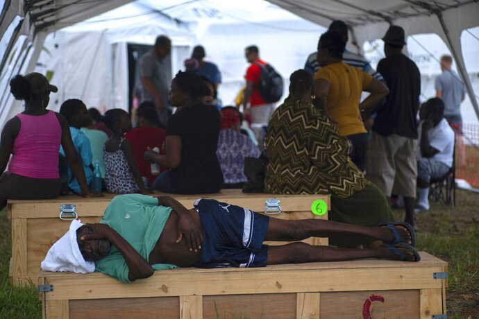 An elderly man waits to be attended at a tent-hospital set up by Samaritan's Purse in the aftermath of Hurricane Dorian in Freeport, Bahamas, Tuesday, Sept. 10, 2019. Thousands of hurricane survivors are facing the prospect of starting their lives over but with little idea of how or where to even begin. (AP Photo/Ramon Espinosa)