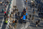 Indian policemen beat farmers driving a tractor after protesting farmers and policemen clash during India's Republic Day celebrations in New Delhi, India, Tuesday, Jan. 26, 2021. (AP Photo/Altaf Qadri)