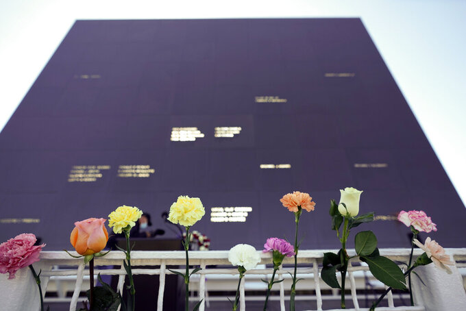 Flowers line the railing placed their by visitors at the Space Mirror Memorial during a ceremony to honor fallen astronauts at the Kennedy Space Center Visitors Complex, Thursday, Jan. 28, 2021, in Cape Canaveral, Fla. The memorial displays the names of astronauts that lost their lives furthering the cause of space exploration. (AP Photo/John Raoux)