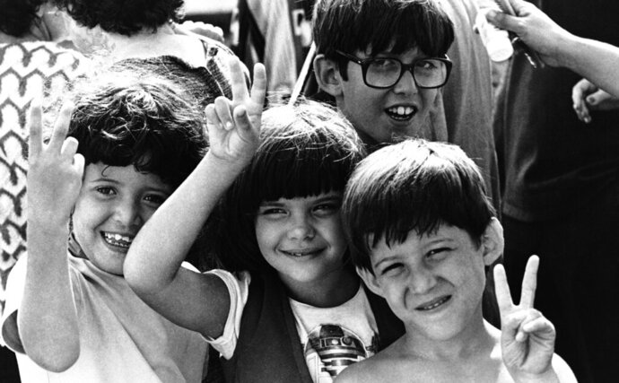 FILE - In this May 21, 1980, file photo, Cuban refugee children flash victory signs after their arrival in Key West, Fla. Throughout history, the United States has used all sorts of physical or mental exams for immigrants seeking just to get into the country outside of becoming a citizen. (AP Photo/Steve Helber, File)