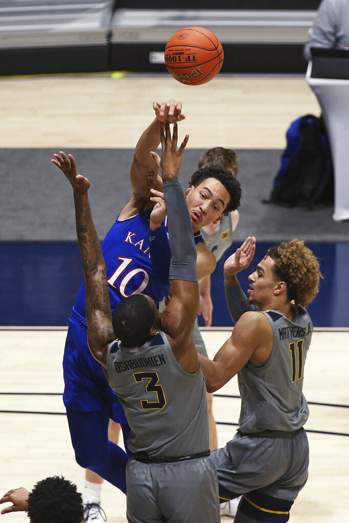 Kansas forward Jalen Wilson (10) passes while defended by West Virginia forwards Gabe Osabuohien (3) and Emmitt Matthews Jr. (11) during the second half of an NCAA college basketball game Saturday, Feb. 6, 2021, in Morgantown, W.Va. (AP Photo/Kathleen Batten)