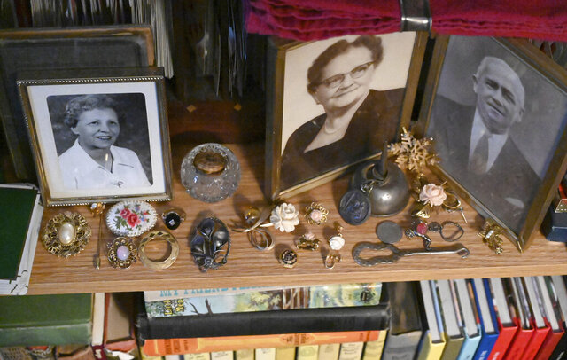 In this Wednesday, Jan. 8. 2020 photo, jewelry is positioned next to old family photos as family heirloom jewelry comprise a portion of Michael Cruz's antique collection at his home in Westminster, Md. (Brian Krista/The Baltimore Sun via AP)